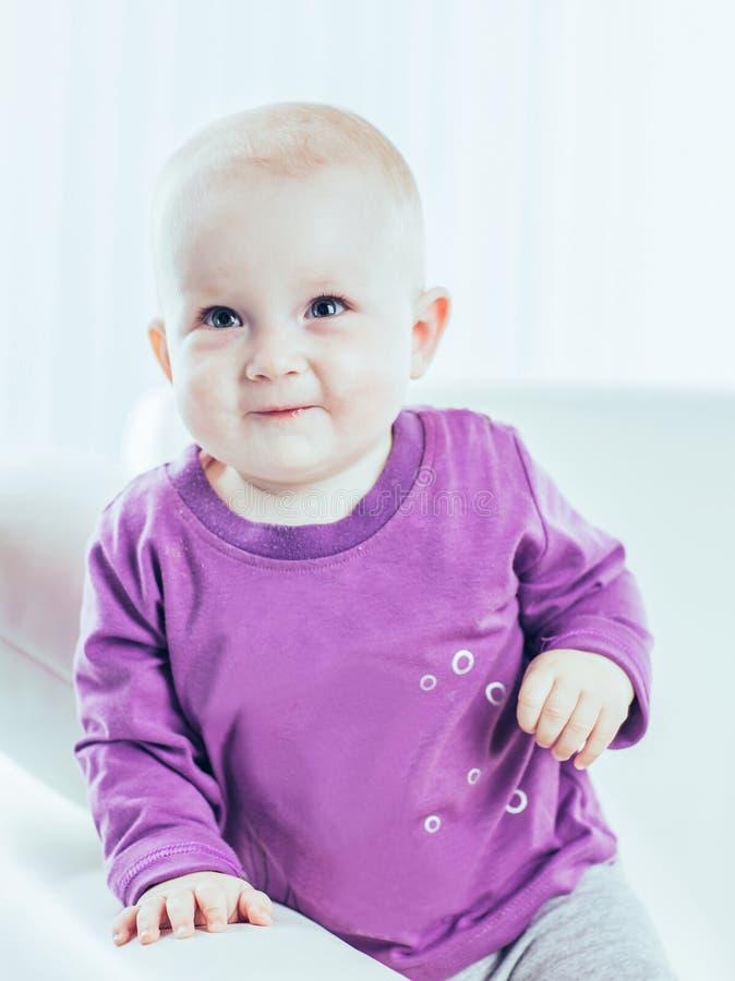 Retrato de un beb? de un a?o feliz en un fondo del sitio brillante del ` s de los ni?os imagenes de archivo