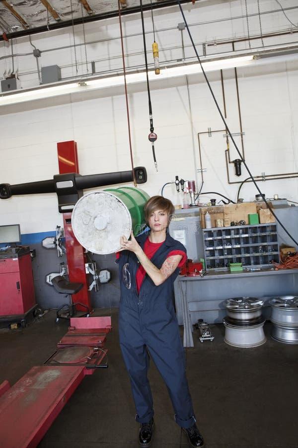 Retrato de un bidón de aceite que lleva del mecánico de sexo femenino joven en hombro en garaje de la reparación auto foto de archivo libre de regalías