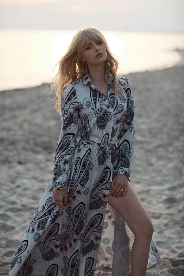 Retrato de un blonde elegante en la playa durante puesta del sol imagen de archivo