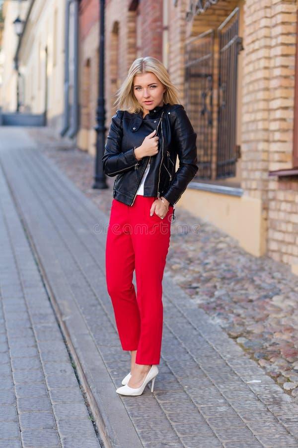 Retrato de un blonde hermoso en pantalones rojos imagen de archivo