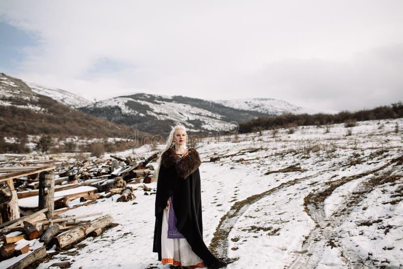 Retrato de un blonde hermoso en un cabo negro, vikingo fotografía de archivo libre de regalías