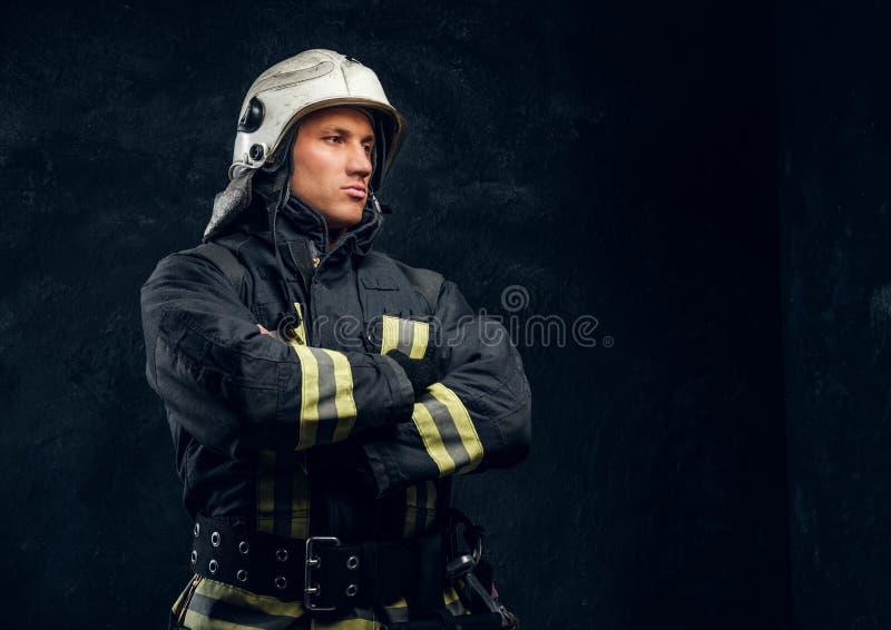 Retrato de un bombero en soportes del uniforme y del casco con las manos cruzadas, mirando de lado con una mirada confiada fotografía de archivo libre de regalías
