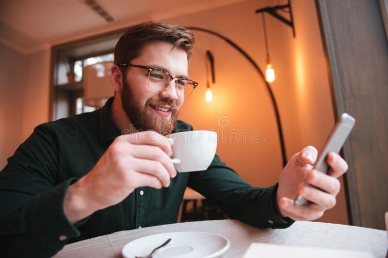 Retrato de un café de consumición barbudo sonriente del hombre joven fotos de archivo