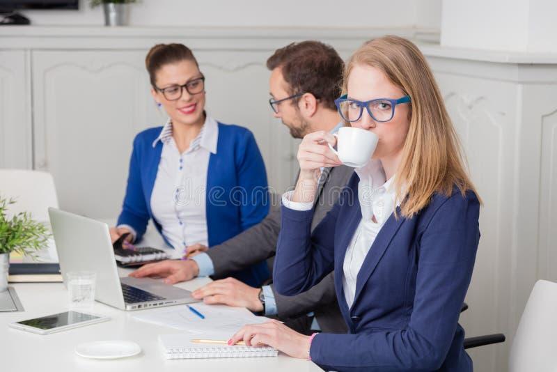 Retrato de un café de consumición de la empresaria joven durante el mee imagen de archivo
