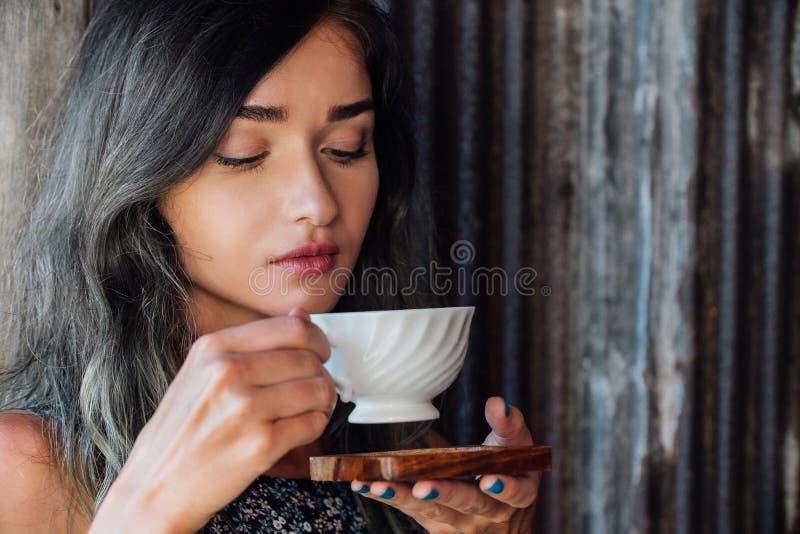 Retrato de un café de consumición de la muchacha en un café del vintage en la terraza en Asia Aspiraciones, bebidas imagenes de archivo