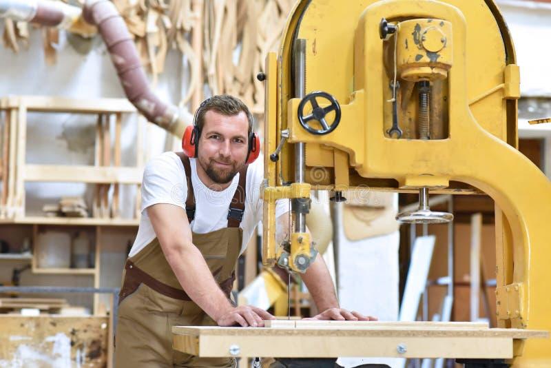 Retrato de un carpintero en la ropa de trabajo y la protección de oído i imagen de archivo libre de regalías