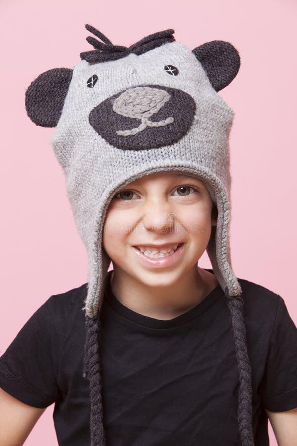 Retrato de un casquillo del mono del muchacho que lleva joven feliz sobre fondo rosado imágenes de archivo libres de regalías