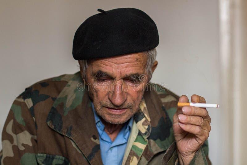 Retrato de un cigarrillo que fuma del viejo hombre foto de archivo libre de regalías