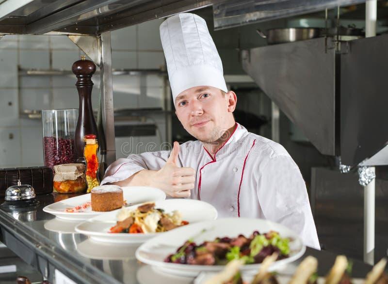 Retrato de un cocinero con alimento cocido en la cocina en el restaurante foto de archivo libre de regalías