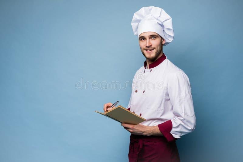 Retrato de un cocinero profesional en libro de la receta de la tenencia del uniforme y de mirar la c?mara en azul claro imágenes de archivo libres de regalías