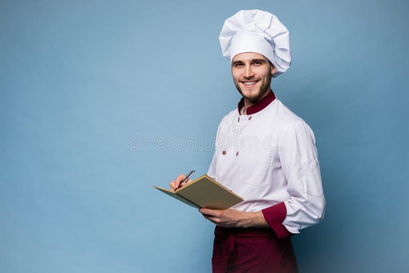 Retrato de un cocinero profesional en libro de la receta de la tenencia del uniforme y de mirar la c?mara en azul claro foto de archivo