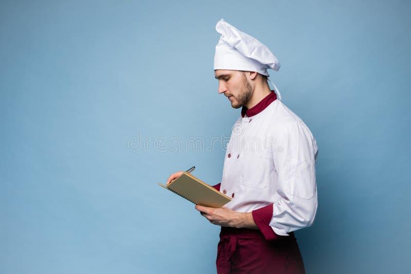 Retrato de un cocinero profesional en libro de la receta de la tenencia del uniforme y de mirar la c?mara en azul claro fotografía de archivo