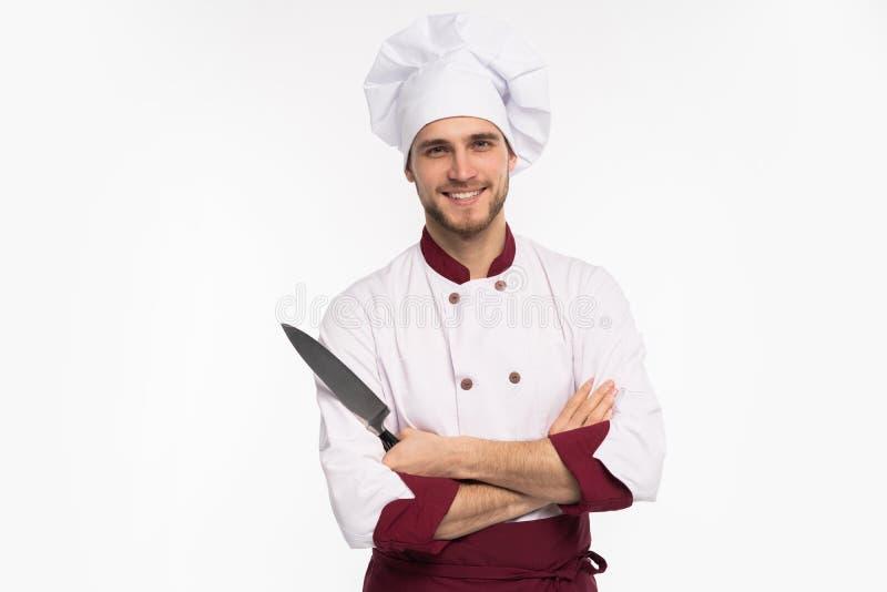 Retrato de un cocinero de sexo masculino hermoso del cocinero que sostiene los cuchillos aislados en un fondo blanco imagenes de archivo