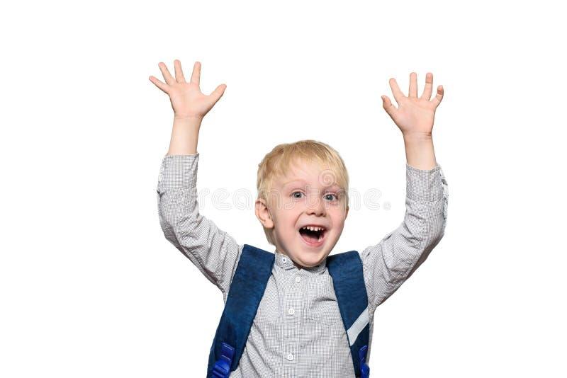 Retrato de un colegial rubio alegre con un bolso de escuela Manos para arriba aislante foto de archivo