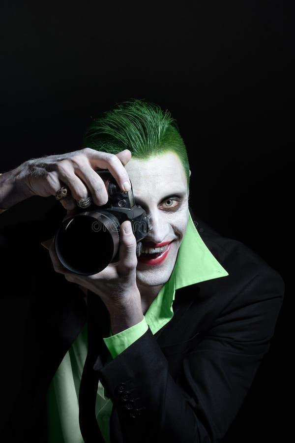 Retrato de un comodín Maquillaje para Halloween Imagen loca de un hombre del fotógrafo en una camisa verde con el pelo verde con fotos de archivo