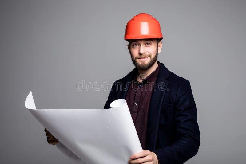 Retrato de un constructor del arquitecto que estudia el plan de los cuartos, ingeniero civil serio de la disposición que trabaja  foto de archivo