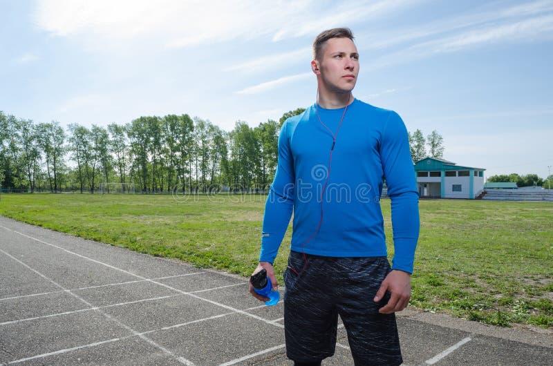 Retrato de un corredor joven en auriculares en el estadio fotografía de archivo