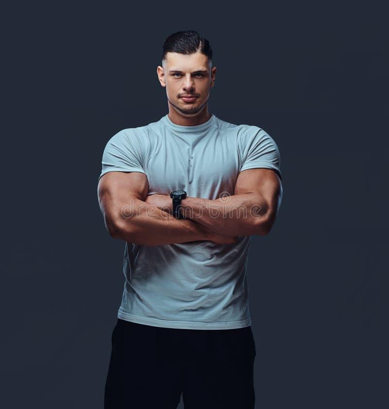 Retrato de un culturista hermoso muscular en ropa de deportes, colocándose con los brazos cruzados en un estudio imagen de archivo libre de regalías