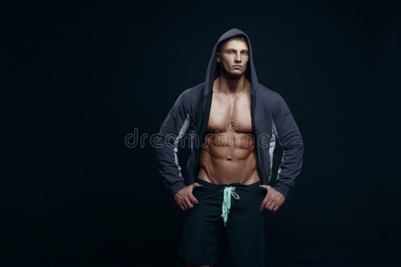 Retrato de un culturista muscular hermoso en la sudadera con capucha que plantea el ove foto de archivo