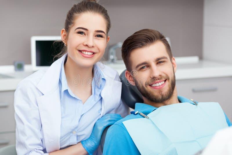 Retrato de un dentista de sexo femenino y de un hombre joven en una oficina del dentista fotografía de archivo libre de regalías