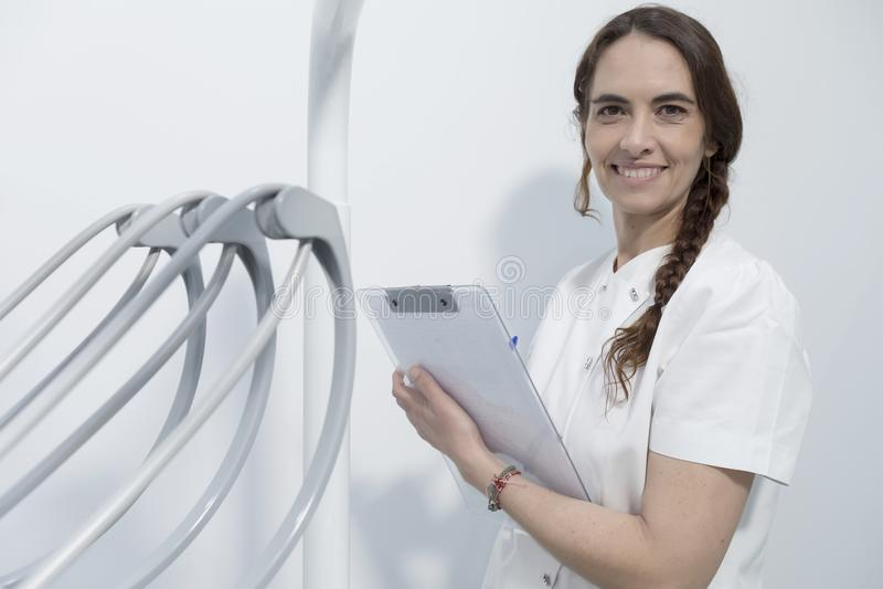 Retrato de un dentista de la mujer joven, registrando en el documento, en el CCB foto de archivo