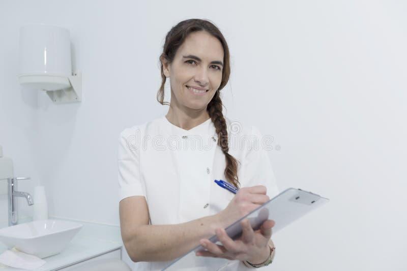 Retrato de un dentista de la mujer joven, registrando en el documento, en el CCB imágenes de archivo libres de regalías