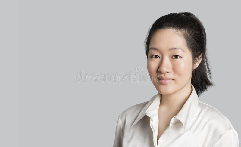 Retrato de un doctor de sexo femenino asiático joven sobre fondo gris fotos de archivo