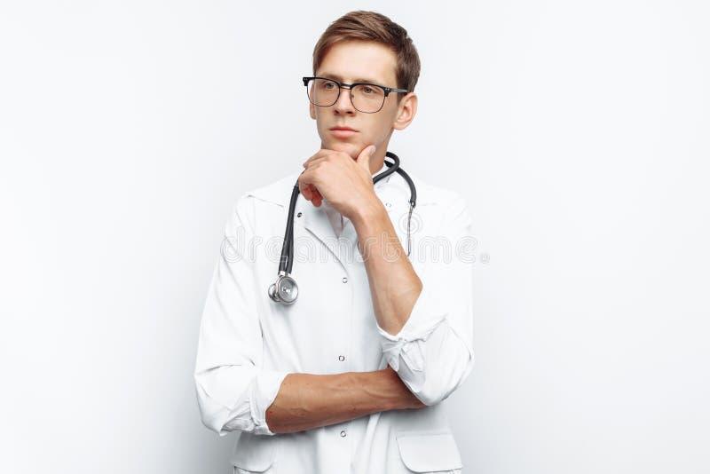 Retrato de un doctor joven, en un fondo blanco, que muestra a un aprendiz pensativo de la mirada en el estudio, con un estetoscop fotos de archivo libres de regalías