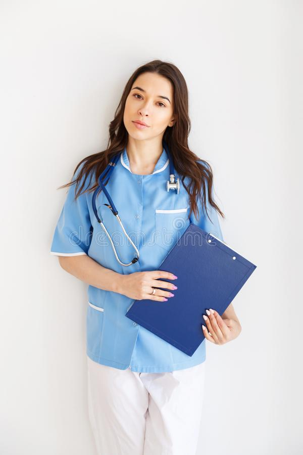 Retrato de un doctor de sexo femenino joven atractivo en capa azul imágenes de archivo libres de regalías