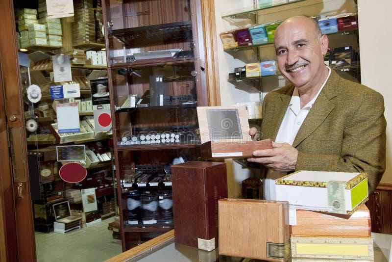 Retrato de un dueño feliz que muestra las cajas de cigarros en tienda fotos de archivo
