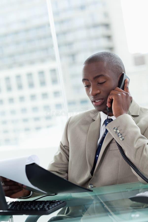 Retrato de un empresario serio que hace una llamada de teléfono mientras que rea foto de archivo libre de regalías