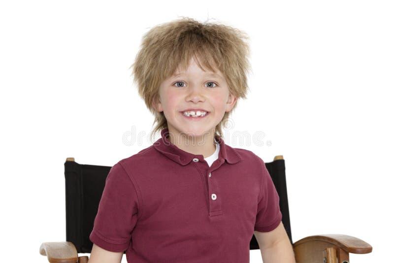 Retrato de un escolar feliz que se sienta en la silla del director sobre el fondo blanco fotografía de archivo