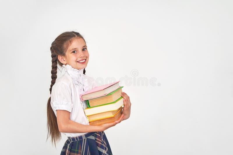Retrato de un estudiante hermoso de la niña con una mochila y una pila de libros en sus manos que sonríe en un fondo blanco imagenes de archivo