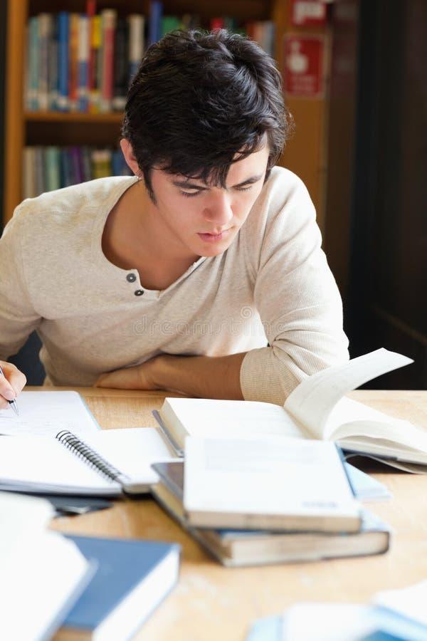 Retrato de un estudiante serio que escribe un ensayo fotos de archivo