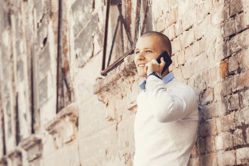 Retrato de un exterior hermoso del hombre joven mientras que habla en un mobi imagenes de archivo