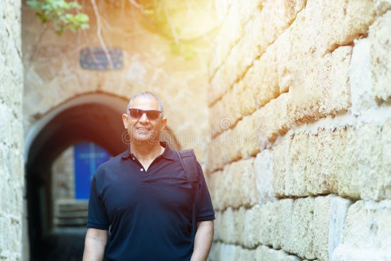 Retrato de un exterior que camina del viejo hombre de negocios turístico confiado foto de archivo libre de regalías