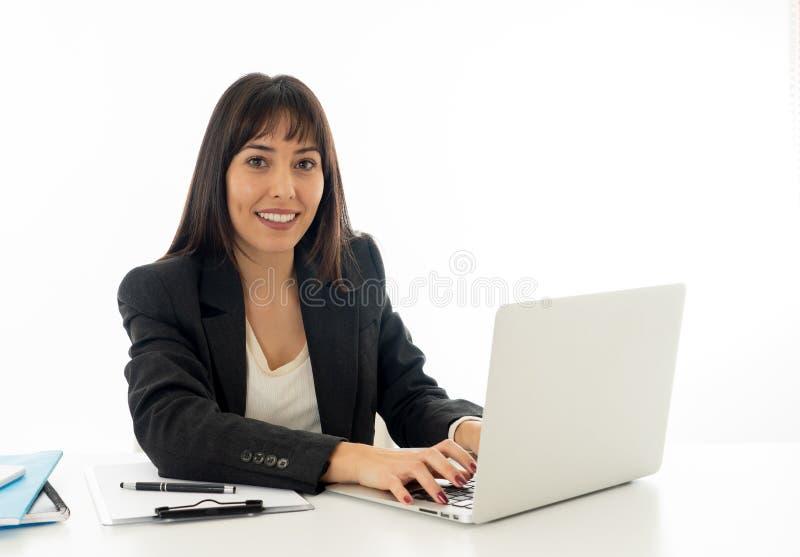 Retrato de un funcionamiento feliz y confiado hermoso joven de la mujer de negocios en el ordenador en la oficina foto de archivo
