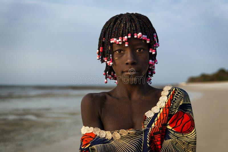 Retrato de un girlr joven hermoso en la playa en la isla de Orango en la puesta del sol fotos de archivo