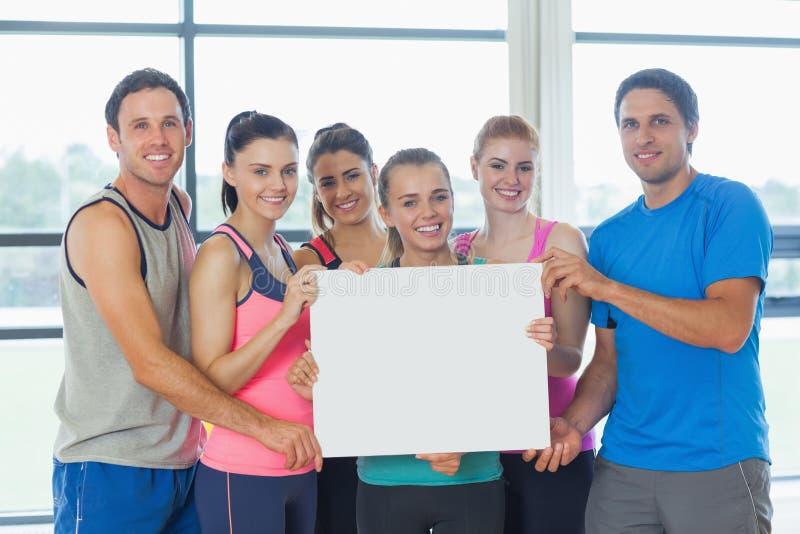 Retrato de un grupo de clase de la aptitud que sostiene el papel en blanco fotografía de archivo