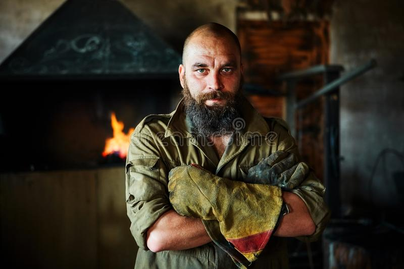 Retrato de un herrero brutal, confiado, hombre con una barba Colocándose en el taller, doblando sus brazos sobre su pecho imagenes de archivo