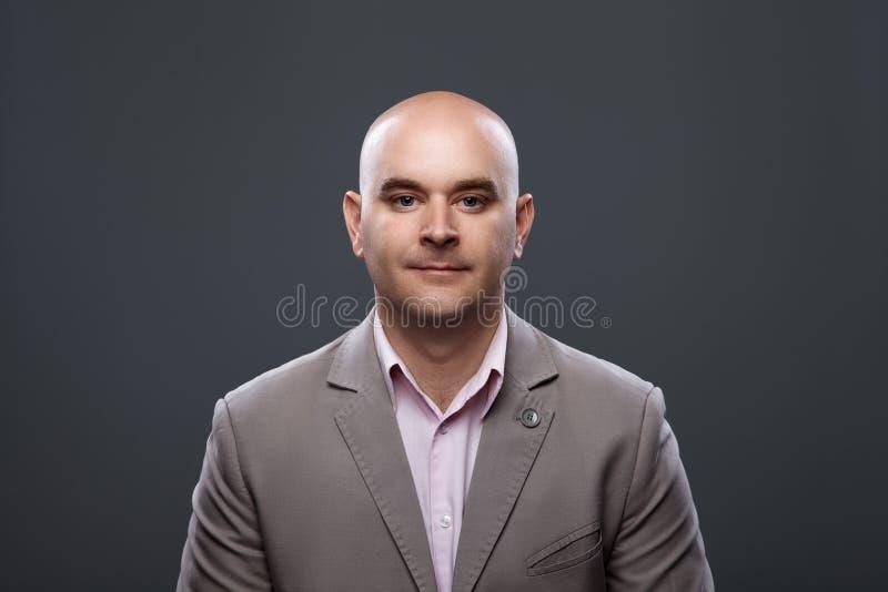 Retrato de un hombre afable calvo en un traje contra un fondo oscuro imágenes de archivo libres de regalías