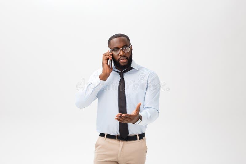 Retrato de un hombre africano joven confuso vestido en la camisa blanca que habla en el teléfono móvil y de gesticular aislado en imagen de archivo libre de regalías