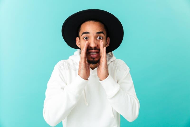 Retrato de un hombre afroamericano joven en sombrero que llama ruidosamente foto de archivo