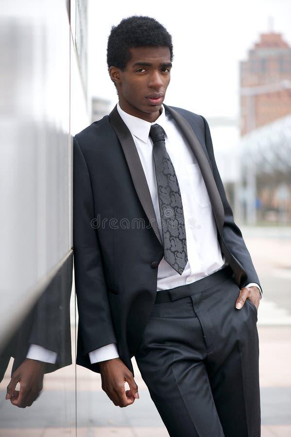 Retrato de un hombre afroamericano joven hermoso que se coloca en la ciudad fotografía de archivo libre de regalías