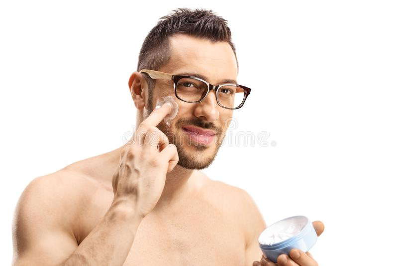 Retrato de un hombre apuesto que se pone crema facial imagenes de archivo