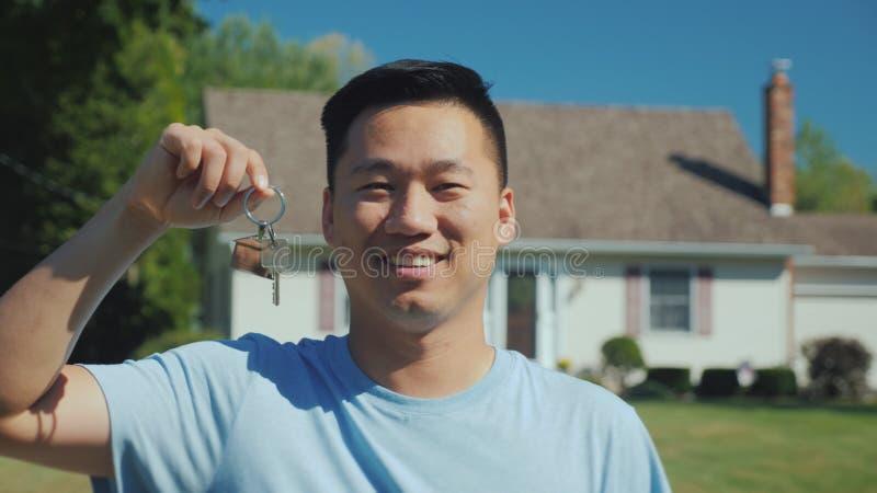 Retrato de un hombre asiático joven con una llave de la casa en su mano Mirada de la cámara contra la perspectiva de su nuevo hog foto de archivo libre de regalías