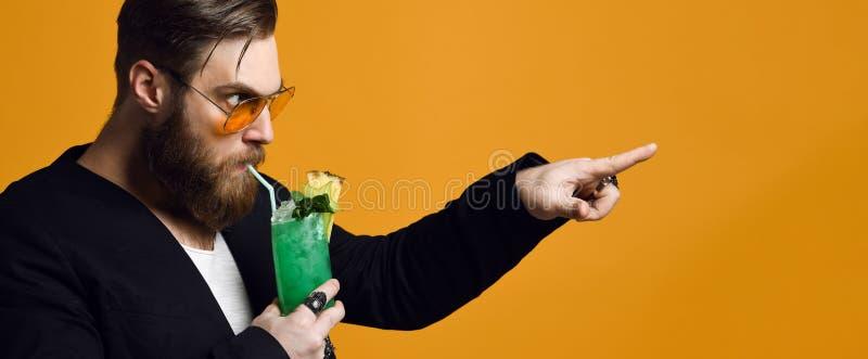 Retrato de un hombre barbudo carism?tico en gafas de sol con un c?ctel en sus manos imagen de archivo