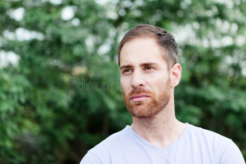 Retrato de un hombre barbudo casual en un parque imagen de archivo