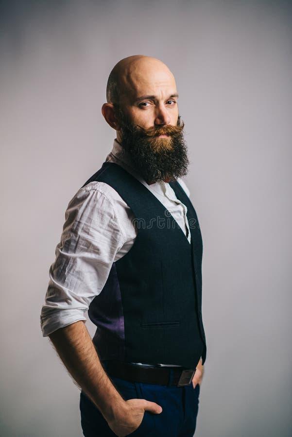 Retrato de un hombre barbudo elegante en un fondo gris foto de archivo