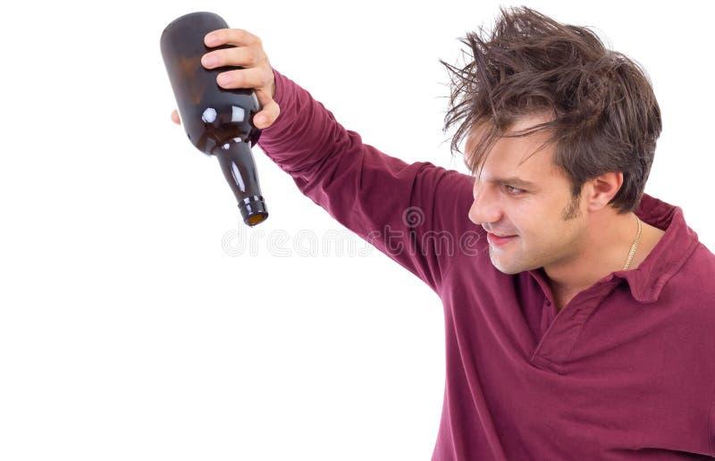 Retrato de un hombre borracho que mira una botella vacía del alcohol imágenes de archivo libres de regalías